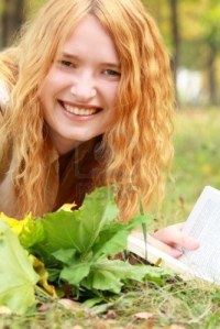 laughing-girl-lying-on-grass-with-a-book