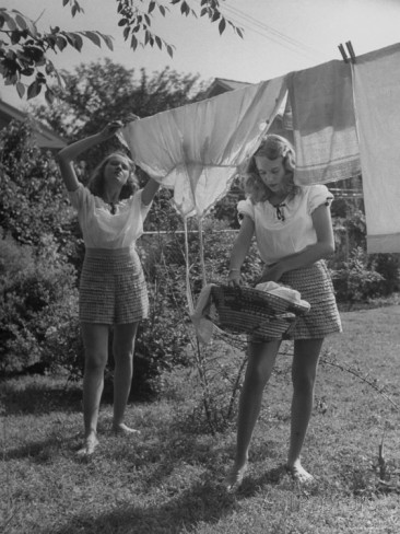 twin-girls-hanging-laundry-on-clothesline