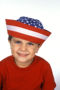 Young boy (4-5) wearing red white and blue sailor hat, smiling, portrait